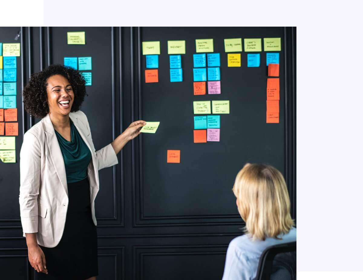 Woman pasting sticky notes on app development workboard