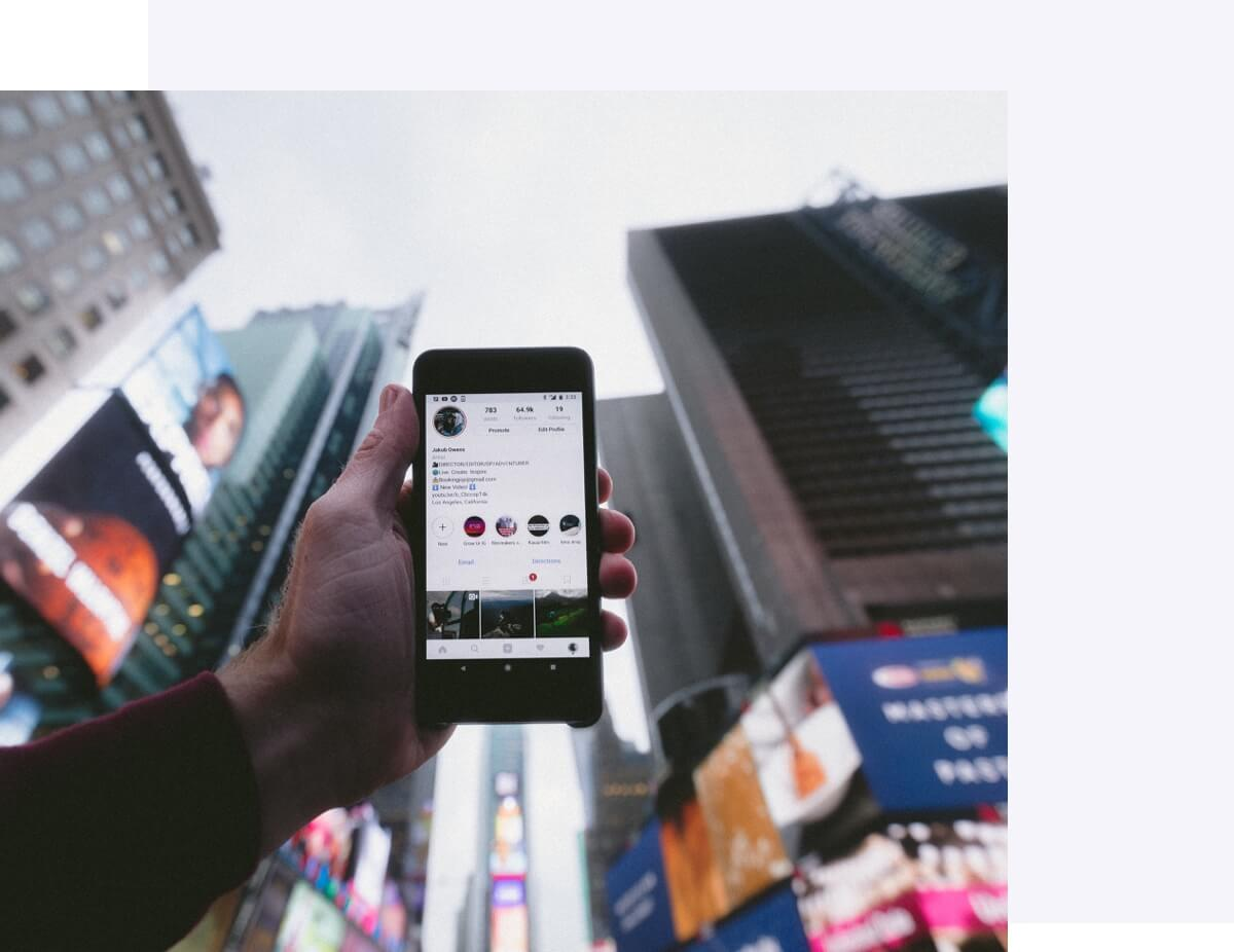 Holding a phone up using Instagram in Times Square